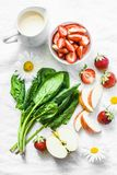 Ingredients for making coconut probiotic yogurt, spinach, apple, strawberry detox smoothie on a light background, top view. Flat lay stock photo