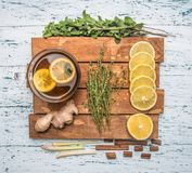 Ingredients for making fragrant tea on a wooden tray, ginger, lemon, mint and cinnamon on a white rustic background, royalty free stock photography