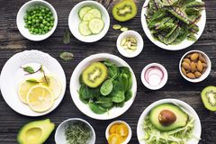 Ingredients for making green salad salads. side dishes, appetizers: sorrel with red veins, spinach, iceberg, pistachios. Avocados, cucumbers, radishes, lemon royalty free stock photography
