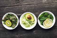 Ingredients for making green salad salads. side dishes, appetizers: sorrel with red veins, spinach, iceberg, pistachios. Avocados, cucumbers, radishes, lemon royalty free stock image