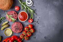 Ingredients for making hamburger. Background. Ground fresh meat patties with seasonings, bun, onion, tomatoes, pickles, ketchup, olive oil, herbs. Burger ready Royalty Free Stock Photography