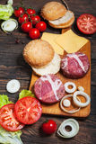 Ingredients for making homemade burger on wooden cutting board Stock Photography
