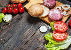 Ingredients for making homemade burger on wooden cutting board Stock Image