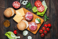 Ingredients for making homemade burger on wooden cutting board. Royalty Free Stock Photo