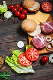 Ingredients for making homemade burger on wooden cutting board. Royalty Free Stock Photography