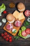 Ingredients for making homemade burger on wooden cutting board. Stock Image