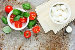 Ingredients for making Italian lasagna caprese - fresh basil, ch. Erry tomatoes, baby mozzarella cheese, fresh pasta on old metal background blank space for text Royalty Free Stock Photography