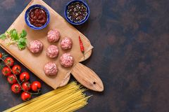 Ingredients for making meatballs with spaghetti on a blue-brown background. Raw meatballs on a cutting board. Top view, copy space.  Royalty Free Stock Photos
