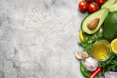 Ingredients for making mexican avocado dip guacamole.Top view wi. Ingredients for making mexican avocado dip guacamole on a slate, stone or concrete background stock image