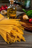 Ingredients for making pasta. On a wooden table: spaghetti, fresh cherry tomatoes, basil leaves, garlic, onions, flavored oil, close view Stock Image