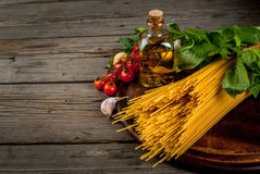 Ingredients for making pasta. On a wooden table: spaghetti, fresh cherry tomatoes, basil leaves, garlic, onions, flavored oil, copy space Royalty Free Stock Images