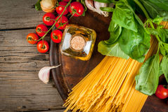 Ingredients for making pasta. On a wooden table: spaghetti, fresh cherry tomatoes, basil leaves, garlic, onions, flavored oil, top close view Stock Images