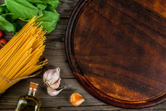 Ingredients for making pasta. On a wooden table: spaghetti, fresh cherry tomatoes, basil leaves, garlic, onions, flavored oil, top view, copy space Stock Image