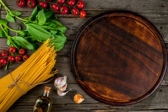 Ingredients for making pasta. On a wooden table: spaghetti, fresh cherry tomatoes, basil leaves, garlic, onions, flavored oil, top view, copy space Royalty Free Stock Photo
