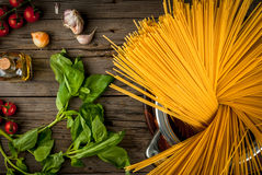 Ingredients for making pasta. On a wooden table: spaghetti, fresh cherry tomatoes, basil leaves, garlic, onions, flavored oil, top view, copy space Stock Photography
