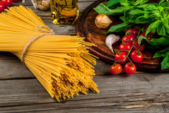 Ingredients for making pasta. On a wooden table: spaghetti, fresh cherry tomatoes, basil leaves, garlic, onions, flavored oil, top view, copy space Royalty Free Stock Images