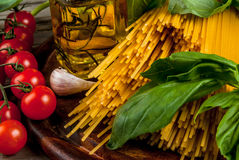 Ingredients for making pasta. On a wooden table: spaghetti, fresh cherry tomatoes, basil leaves, garlic, onions, flavored oil, top view, copy space Royalty Free Stock Image
