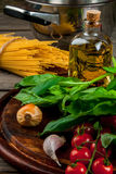 Ingredients for making pasta. On a wooden table: spaghetti, fresh cherry tomatoes, basil leaves, garlic, onions, flavored oil, top view, copy space Royalty Free Stock Photography