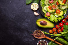 Ingredients for making salad. On rustic black chalk board background. Vegetable salad in bowl, avocado, tomato, cucumber, spinach. Healthy, clean eating concept Royalty Free Stock Photography