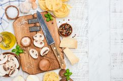 Ingredients for making tagliatelle pasta with mushrooms. Healthy Italian food. Top view, copy space Stock Images