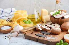Ingredients for making tagliatelle pasta with mushrooms. Healthy Italian food. Selective focus Stock Image