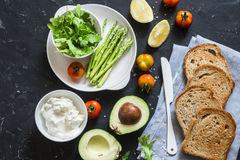 Ingredients for making toast sandwiches with avocado, asparagus, tomatoes and soft cheese on dark background, top view. Royalty Free Stock Image