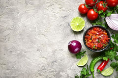 Ingredients for making tomato salsa salsa roja.Top view with c. Ingredients for making tomato salsa salsa roja - traditional mexican sauce on a grey slate,stone stock images
