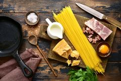 Ingredients for making traditional italian spaghetti carbonara.T. Ingredients for making traditional italian spaghetti carbonara on an old rustic wooden Stock Photography