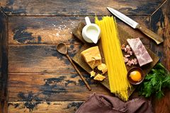 Ingredients for making traditional italian spaghetti carbonara.T. Ingredients for making traditional italian spaghetti carbonara on an old rustic wooden Royalty Free Stock Images