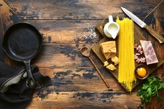 Ingredients for making traditional italian spaghetti carbonara.T. Ingredients for making traditional italian spaghetti carbonara on an old rustic wooden Royalty Free Stock Photography
