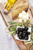 Ingredients for mediterranean breakfast: fresh bread, feta cheese, olives and virgin extra oil. On wooden background Stock Photo