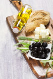 Ingredients for mediterranean breakfast: fresh bread, feta cheese, olives and virgin extra oil. On wooden background Stock Images