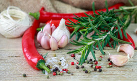 Ingredients of Mediterranean cuisine - garlic, pepper, rosemary and spices. On old wooden table Stock Photo