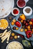 Ingredients for Mexican vegetarian quesadilla on the dark table. Tomato, pepper, paprika, chilli, corn, tortilla, cheese, oil, ket royalty free stock photo