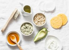 Ingredients for moisturizing, nourishing, anti-aging wrinkle face mask - avocado, olive oil, oatmeal, natural yogurt on light back. Ground, top view. Homemade stock photos