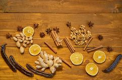 Ingredients for mulled wine: dried fruits, orange, carob, ginger, sticks of cinnamon, anise stars, nuts on wooden brown background Royalty Free Stock Images