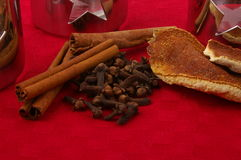 Ingredients for mulled wine on red cloth. Ingredients for mulled wine - cinnamon, cloves, orange peel - on red table cloth with glasses in background Stock Photos