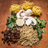 Ingredients  nest pasta walnuts raisins herbs mushrooms on a cutting board wooden rustic background close up Stock Images