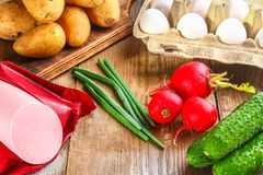 Ingredients for okroshki - sausage, eggs, radishes, onions, pota. Toes, cucumbers on an old wooden table Royalty Free Stock Photography