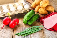 Ingredients for okroshki - sausage, eggs, radishes, onions, potatoes, cucumbers on an old wooden table. Ingredients for okroshki - sausage, eggs, radishes Royalty Free Stock Photography