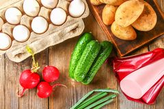 Ingredients for okroshki - sausage, eggs, radishes, onions, potatoes, cucumbers on an old wooden table. Ingredients for okroshki - sausage, eggs, radishes Stock Photography