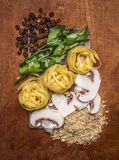 Ingredients for pasta cooking herbs raisins mushrooms chopped walnuts lines laid out  a chopping board on wooden background top Stock Photography
