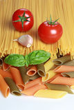 Ingredients for a pasta meal. Including tomatoes, garlic, basil and different kind of pasta royalty free stock image