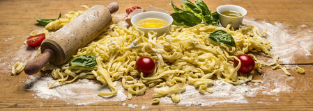 Ingredients for pasta, rolling pin flour butter eggs tomatoes herbs close up  on wooden rustic background Stock Image