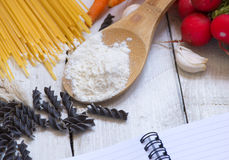 Ingredients for pasta: spaghetti, vegetables and spices and a notepad on the old table Stock Photo