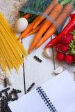 Ingredients for pasta: spaghetti, vegetables and spices and a notepad on the old table Royalty Free Stock Photos
