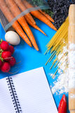 Ingredients for pasta: spaghetti, vegetables and spices and a notepad on the old table Royalty Free Stock Photo