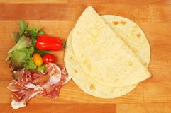 Ingredients for a piadini. Igredients for a piadini on a wooden chopping board, top view Royalty Free Stock Photography