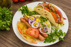 Ingredients for a picnic consisting of vegetables and sausages grilled on wooden rustic background, top view. Close-up Stock Images