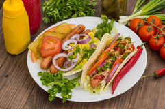 Ingredients for a picnic consisting of vegetables and sausages grilled on wooden rustic background, top view. Close-up Stock Photography